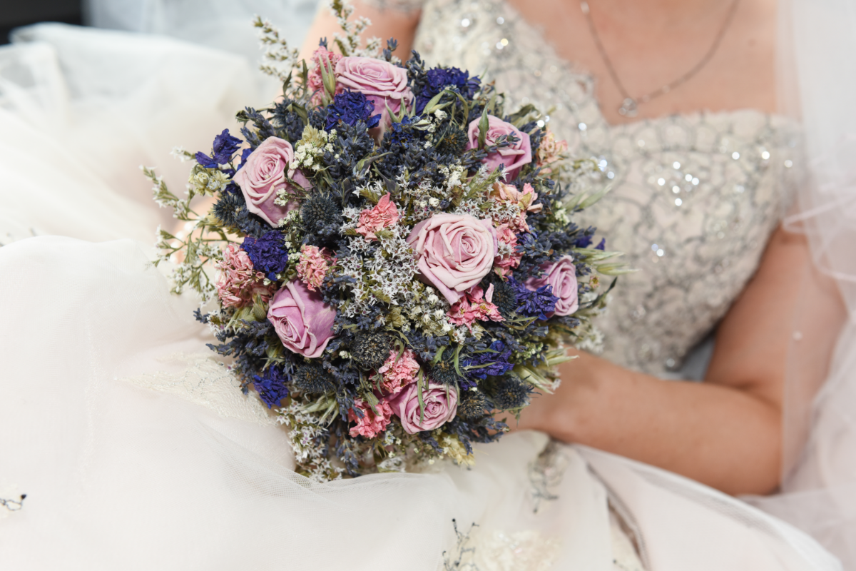 rustic bouquet with pale pink roses held by a bride with a sparkly lace corset dress